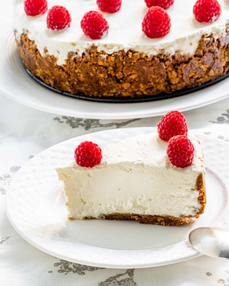 a slice of no bake cheesecake topped with raspberries on a white plate