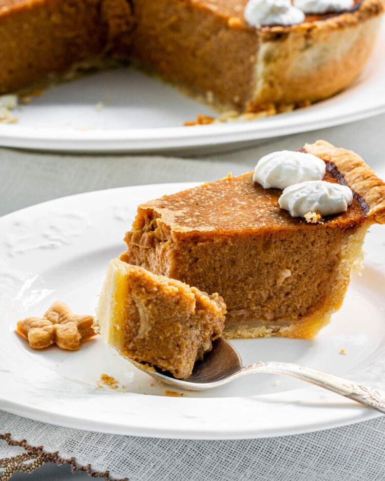 a slice of pumpkin pie on a white plate with a bite in a spoon