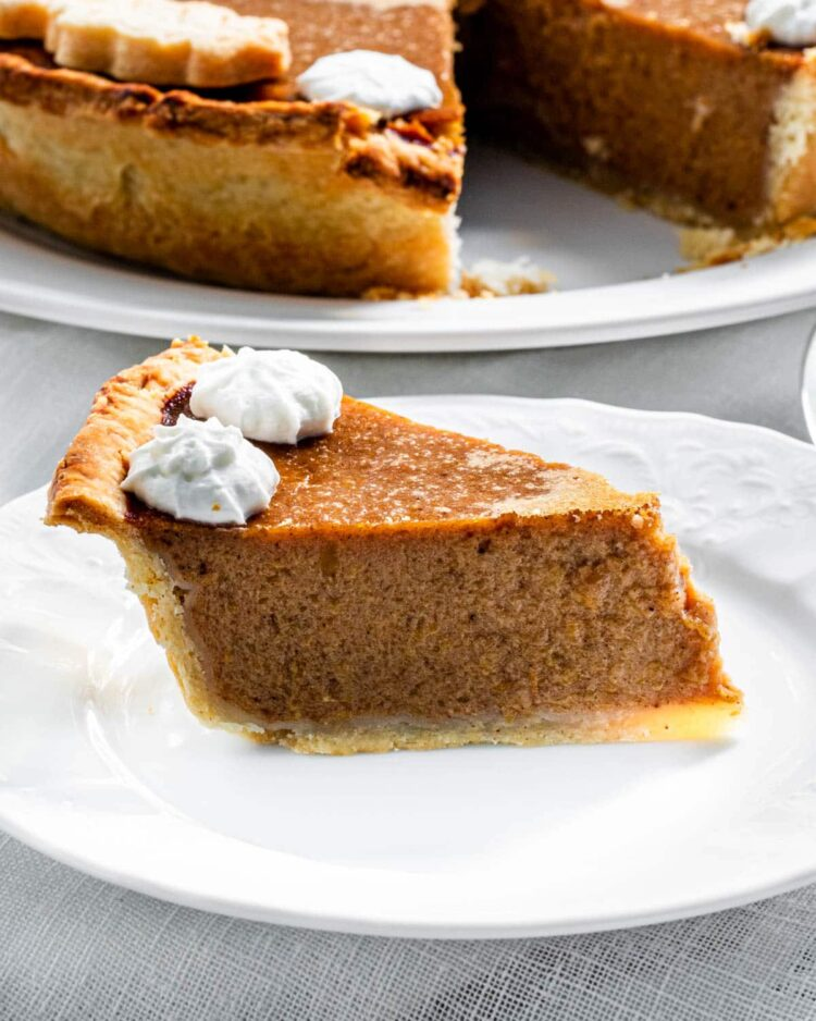 a slice of pumpkin pie on a white plate with 2 dollops of whipped cream