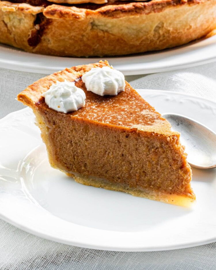 a slice of pumpkin pie on a white plate