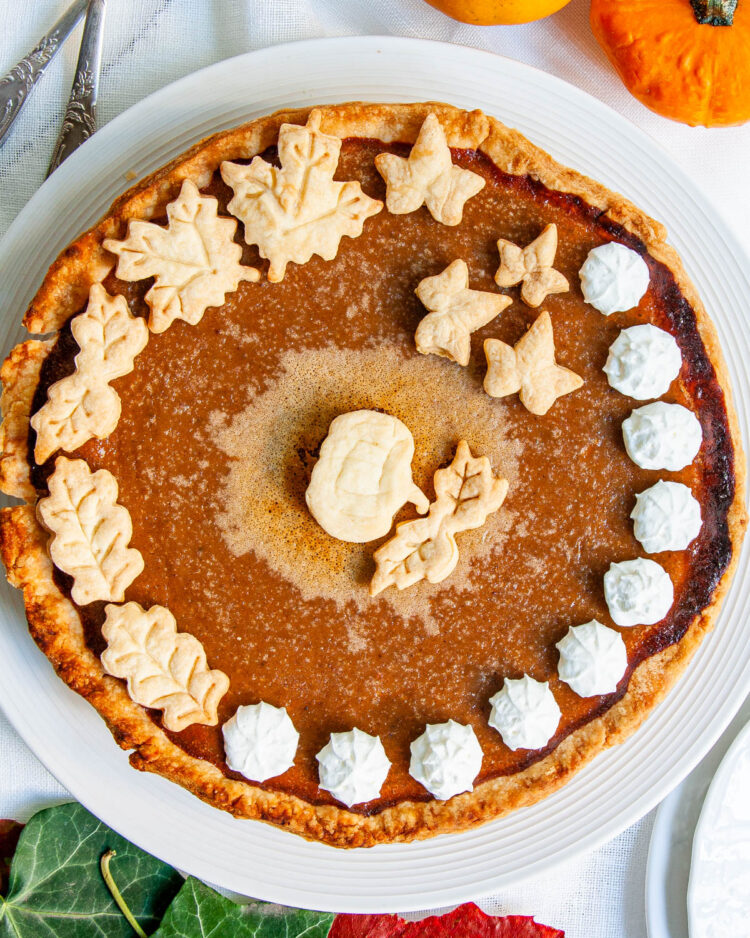 overhead shot of a baked pumpkin pie on a white serving plate