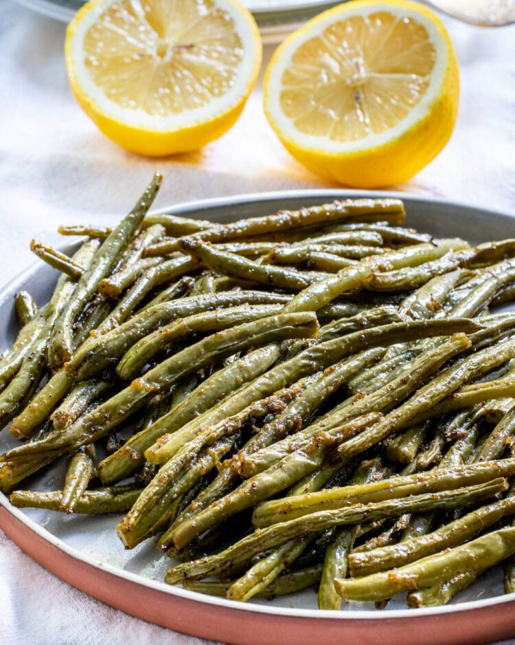 roasted green beans on a plate with 2 lemon halves in the background