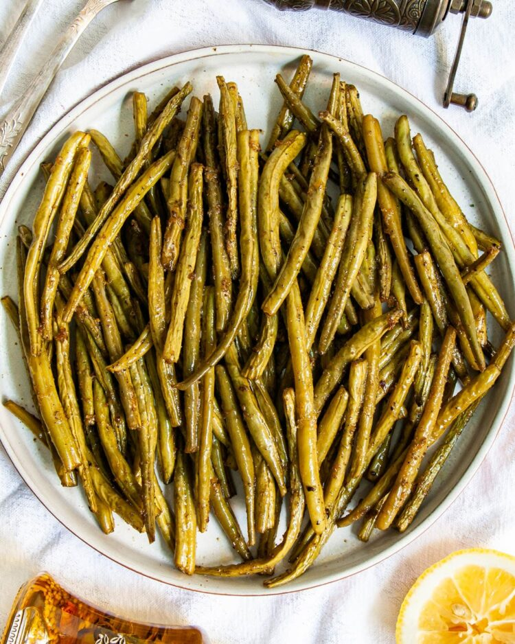 overhead shot of roasted green beans on a plate