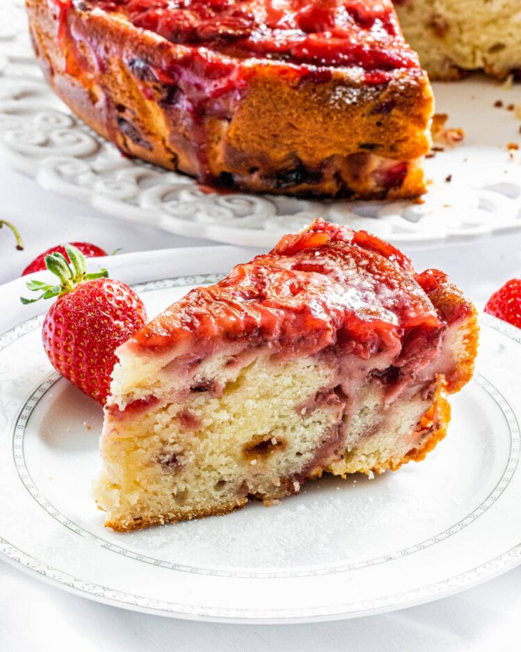 a slice of strawberry cake on a white plate with the whole cake in the background on a platter