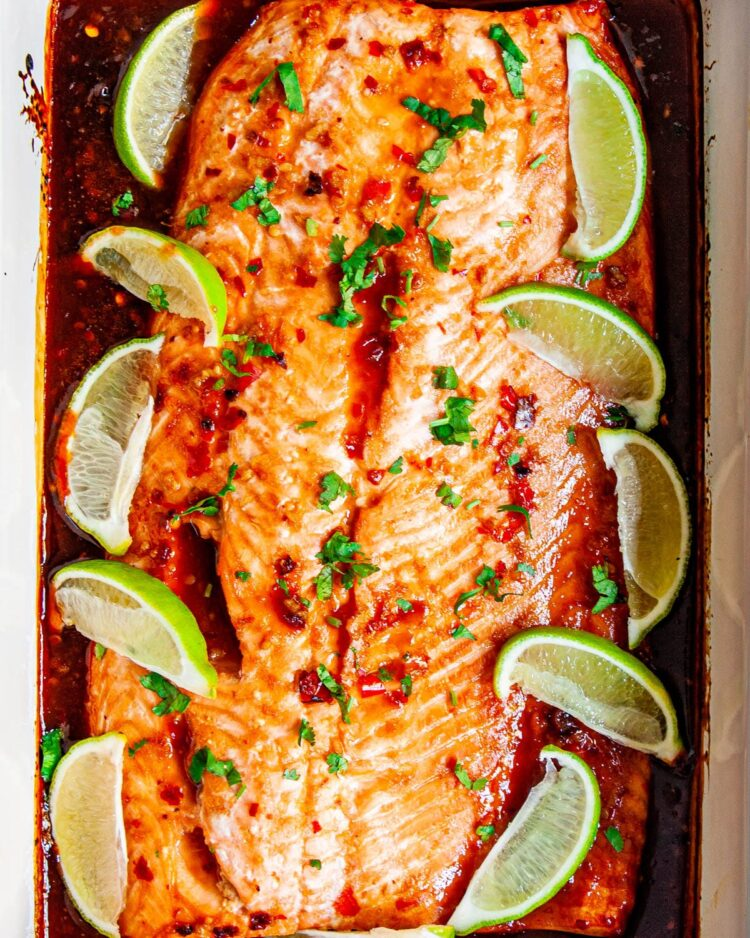 overhead shot of thai salmon baked in a  casserole dish garnished with lime wedges