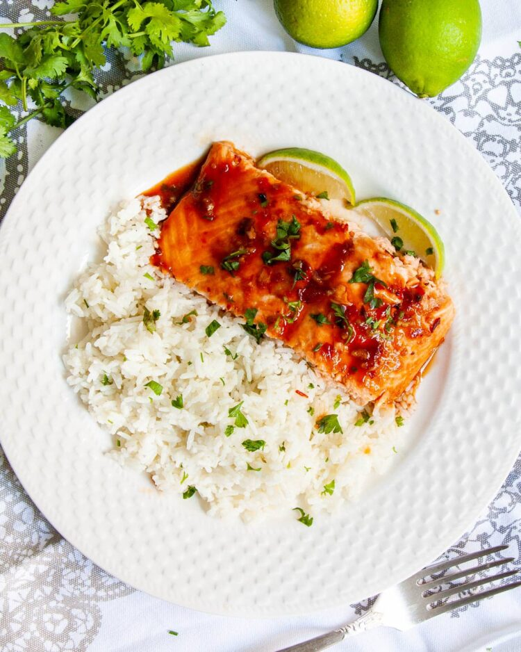 overhead shot of a slice of thai salmon with rice on a white plate