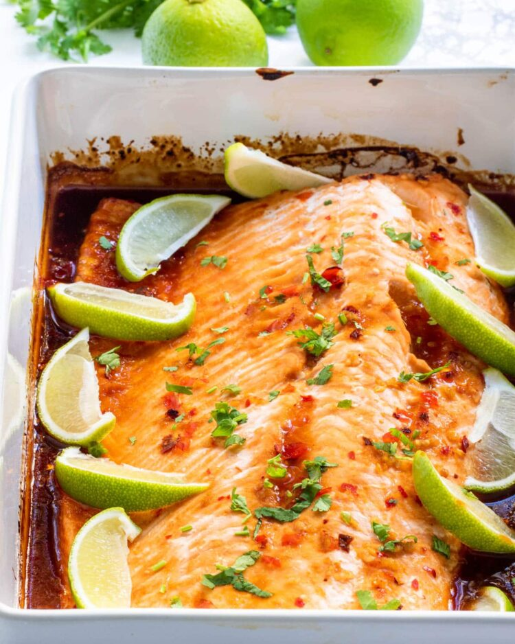 thai salmon in a casserole dish with lime wedges