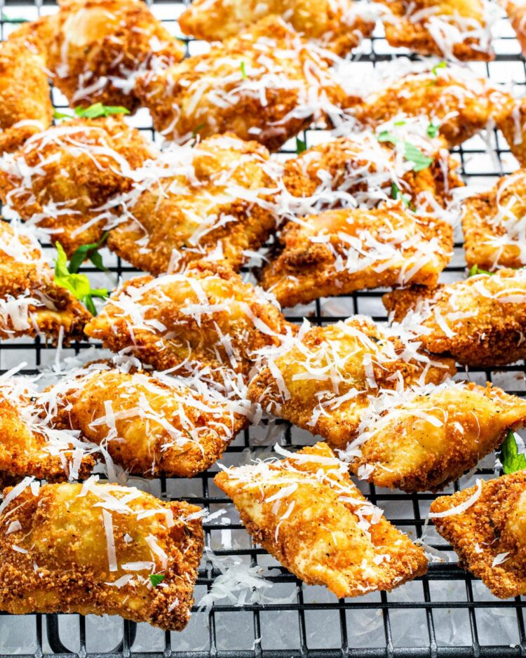 fried ravioli on a cooling rack garnished with parsley and parmesan cheese