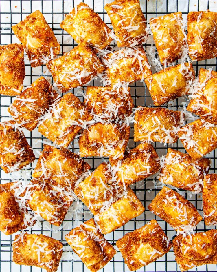 toasted ravioli on a cooling rack garnished with parmesan cheese