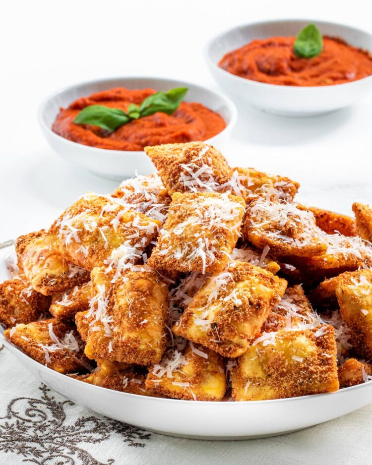 a large bowl loaded with toasted ravioli and 2 little bowls with marinara sauce in the background