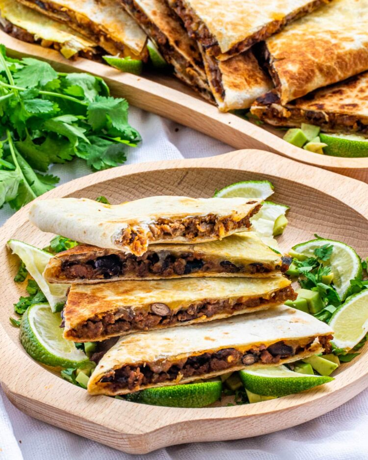 beef quesadillas cut into wedges on a wooden plate