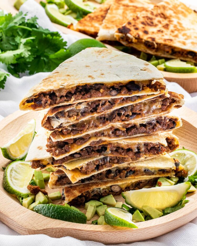 a stack of cheese beef quesadillas on a wooden plate garnished with limes and avocados