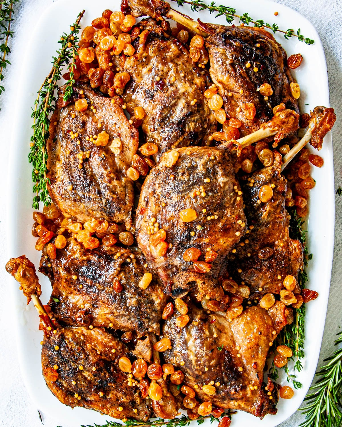 overhead shot of duck confit on a serving platter with pickled raisins and garnished with thyme