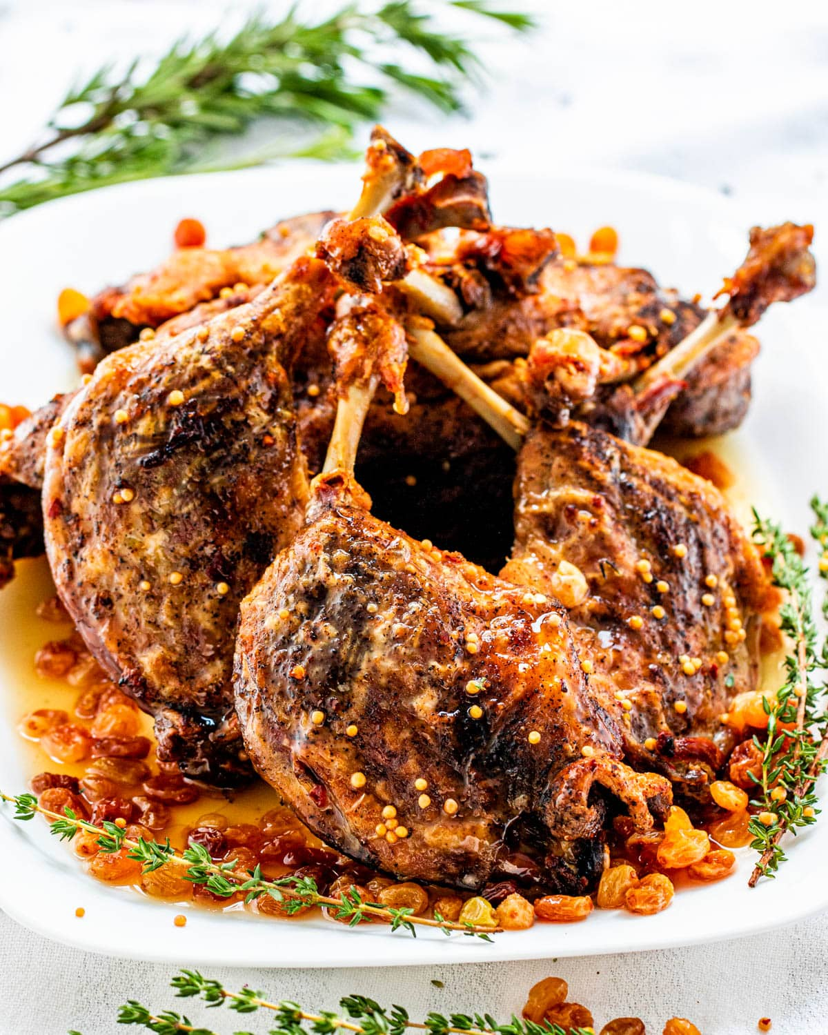duck confit legs with pickled raisins on a white serving platter