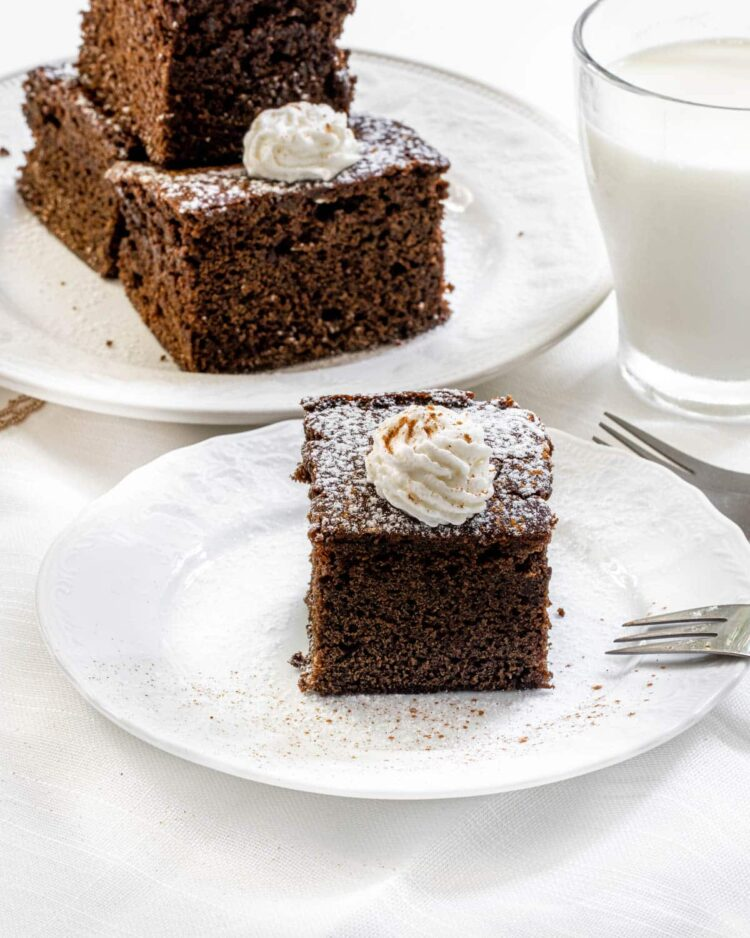 a slice of gingerbread cake with a dollop of whipped cream with a glass of milk in the background