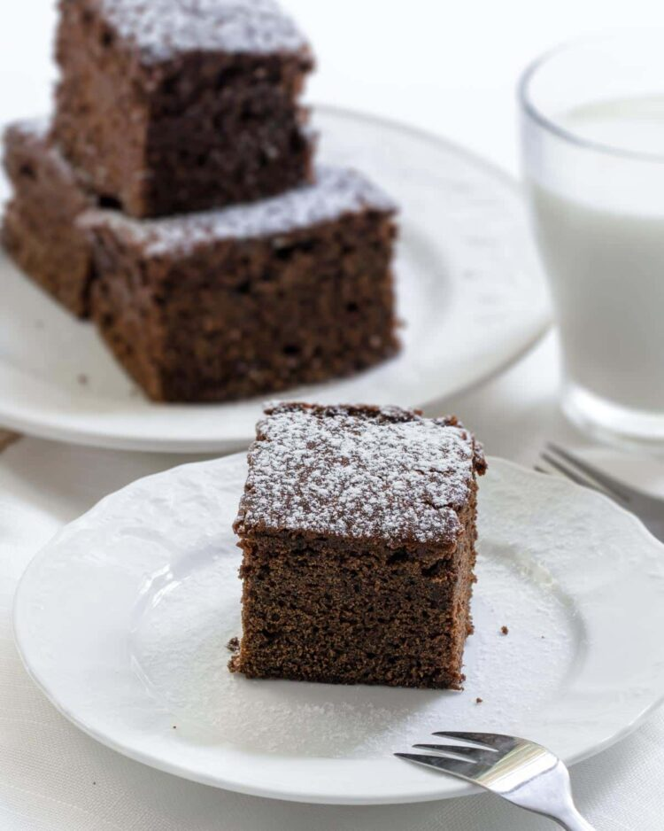 a slice of gingerbread cake on a plate sprinkled with powdered sugar