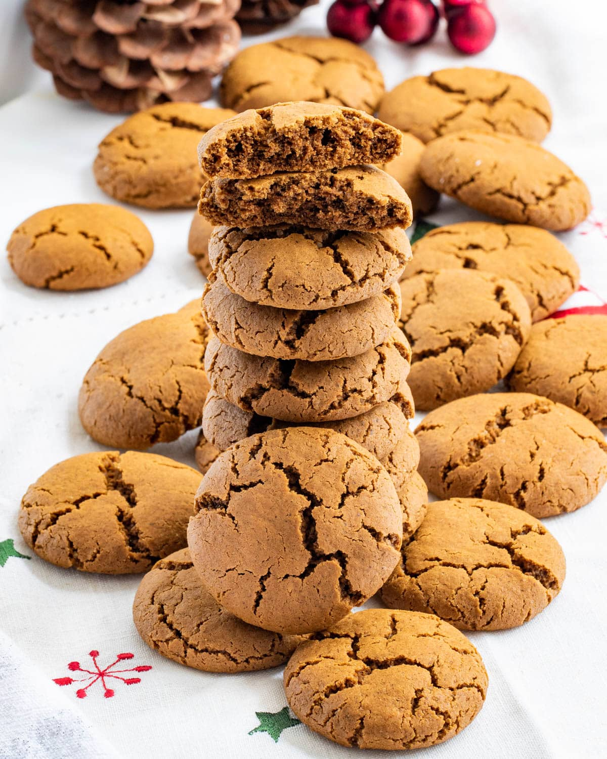 stack of chewy gingerbread cookies on a Christmas-themed table cloth.