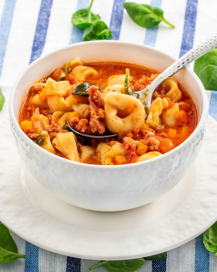 tortellini soup in a white bowl with a spoon inside