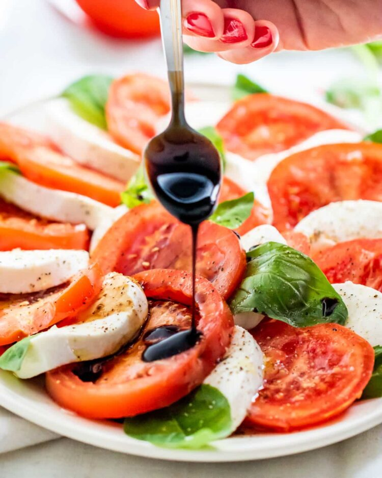 a spoon with balsamic glaze drizzling some over caprese salad