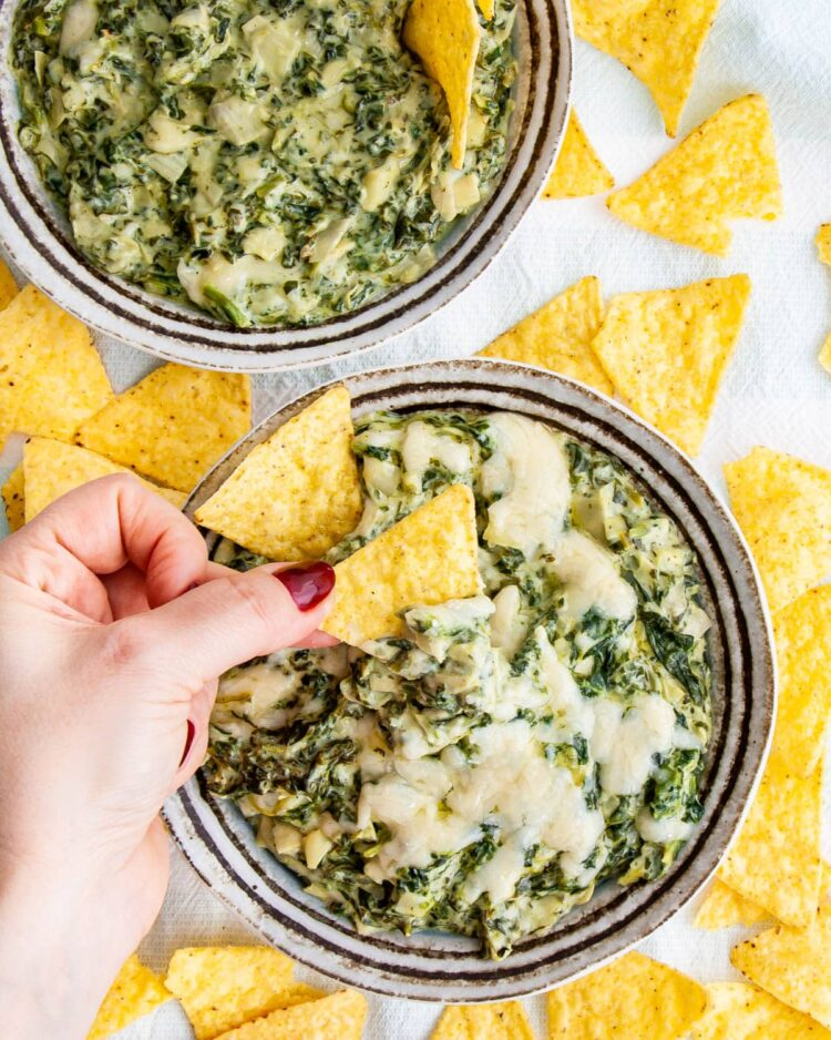 overhead shot of two bowls with spinach dip surrounded by tortilla chips