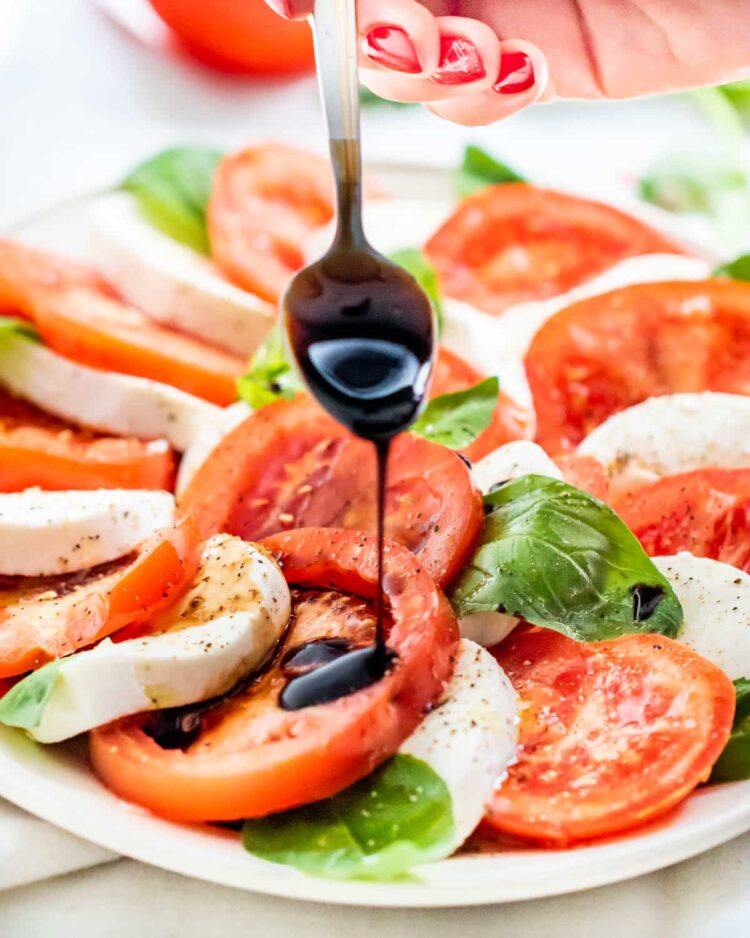 a hand holding a spoon drizzling balsamic glaze over caprese salad