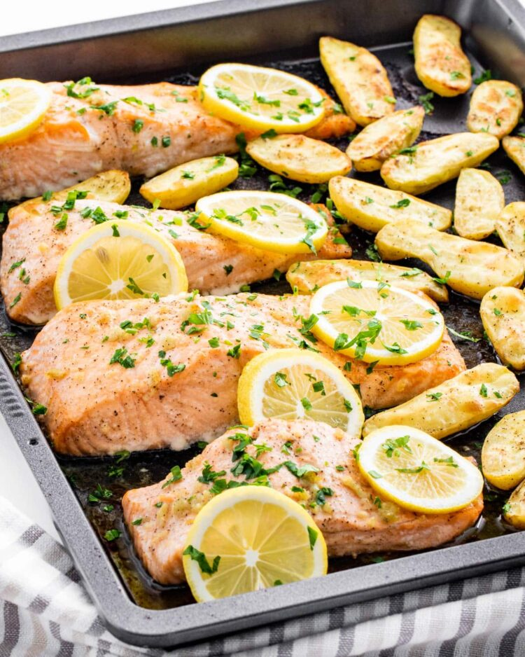 garlic butter baked salmon and fingerling potatoes on a baking sheet