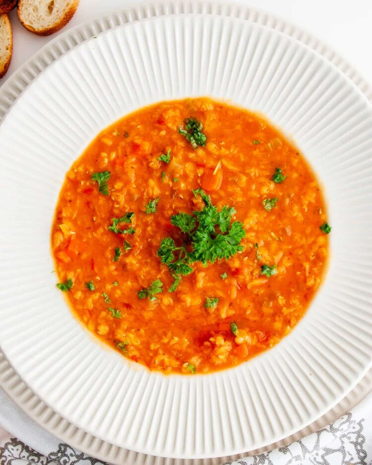 lentil soup garnished with parsley in a white bowl
