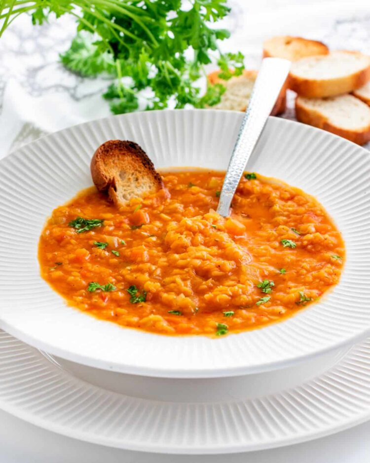 lentil soup in a white plate with toasted bread and a spoon