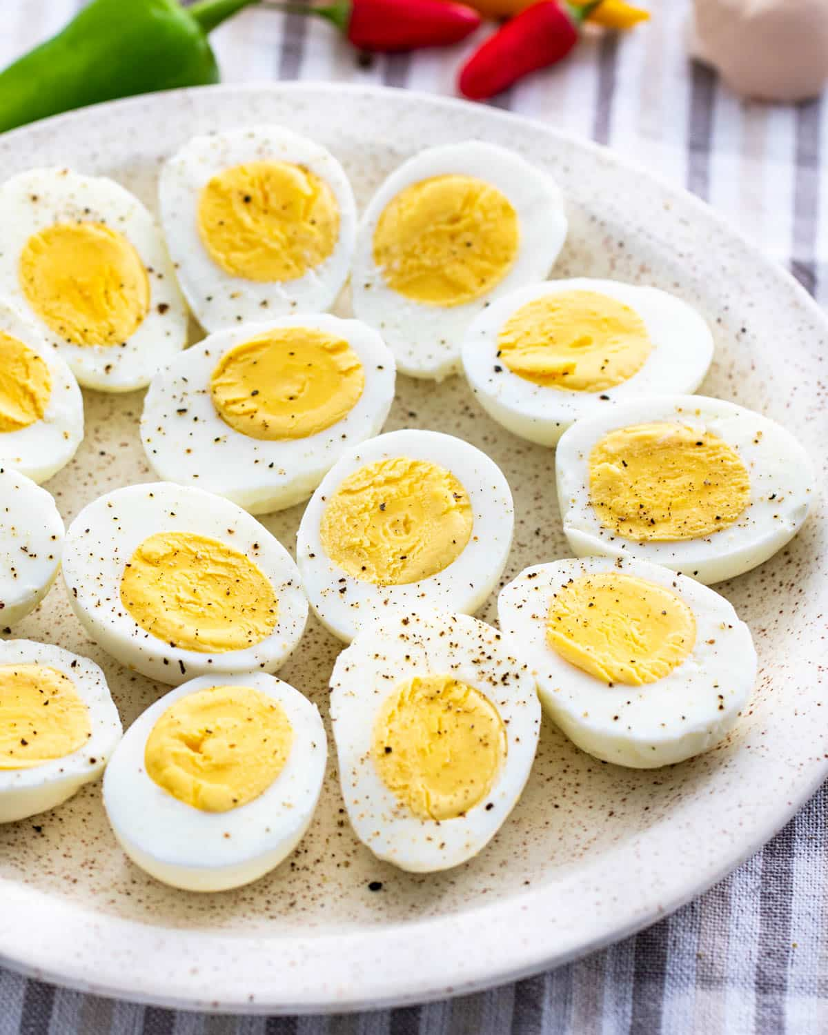 hard boiled eggs peeled and cut in half on a white plate