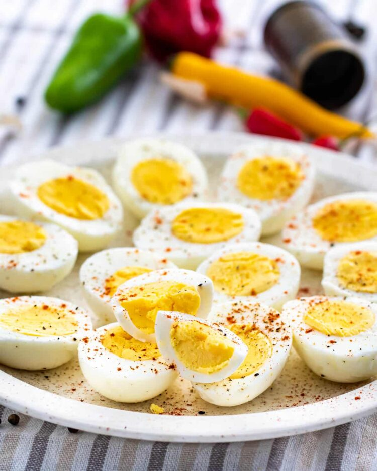 a plate full of hard boiled eggs cut in half sprinkled with spices