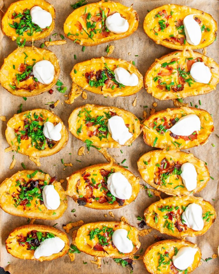 overhead shot of potato skins on a baking sheet garnished with sour cream and chives