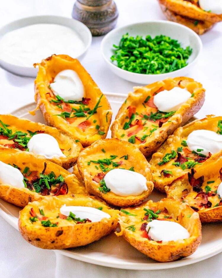 potato skins garnished with sour cream, chives and bacon on a white platter