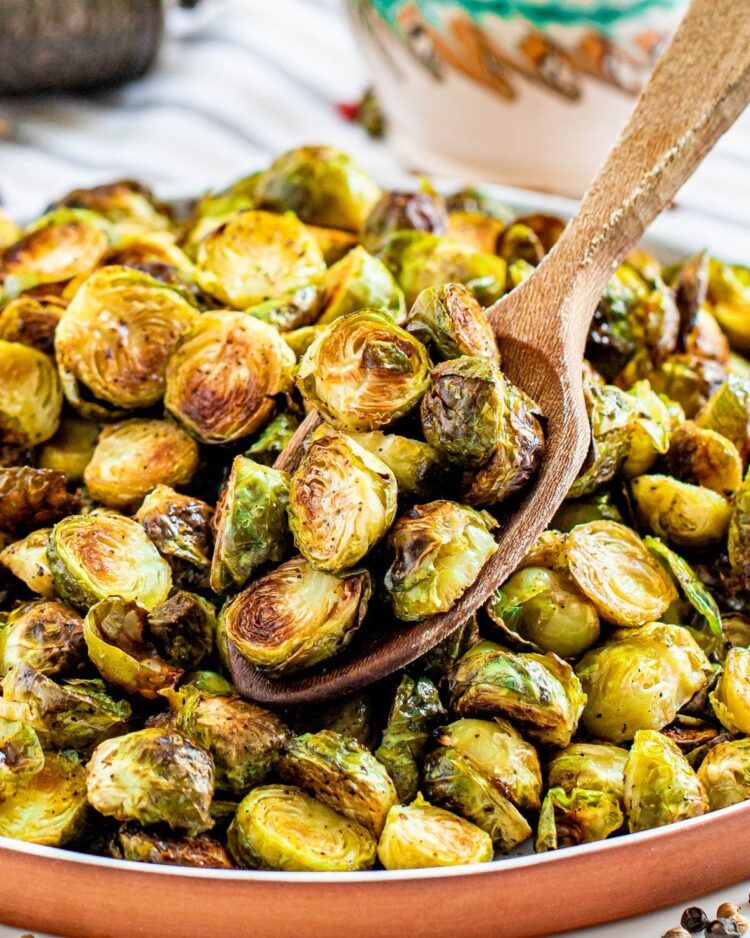 a spoon holding some roasted brussels sprouts over a plate loaded with them