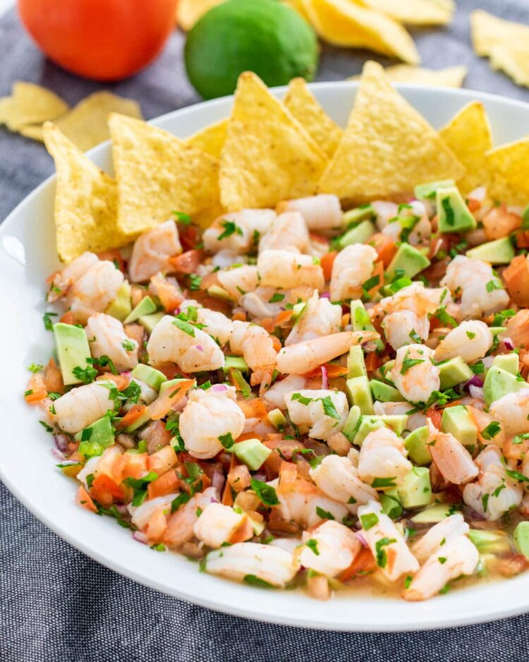 a white bowl full of shrimp ceviche and tortilla chips on the side