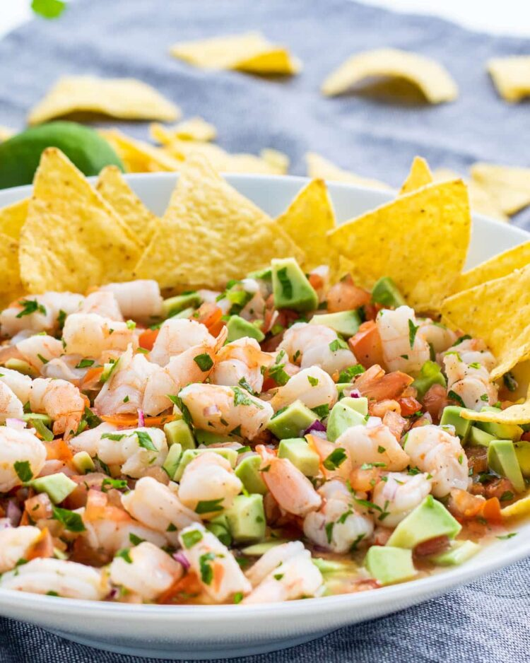 shrimp ceviche in a white bowl with tortilla chips on the side