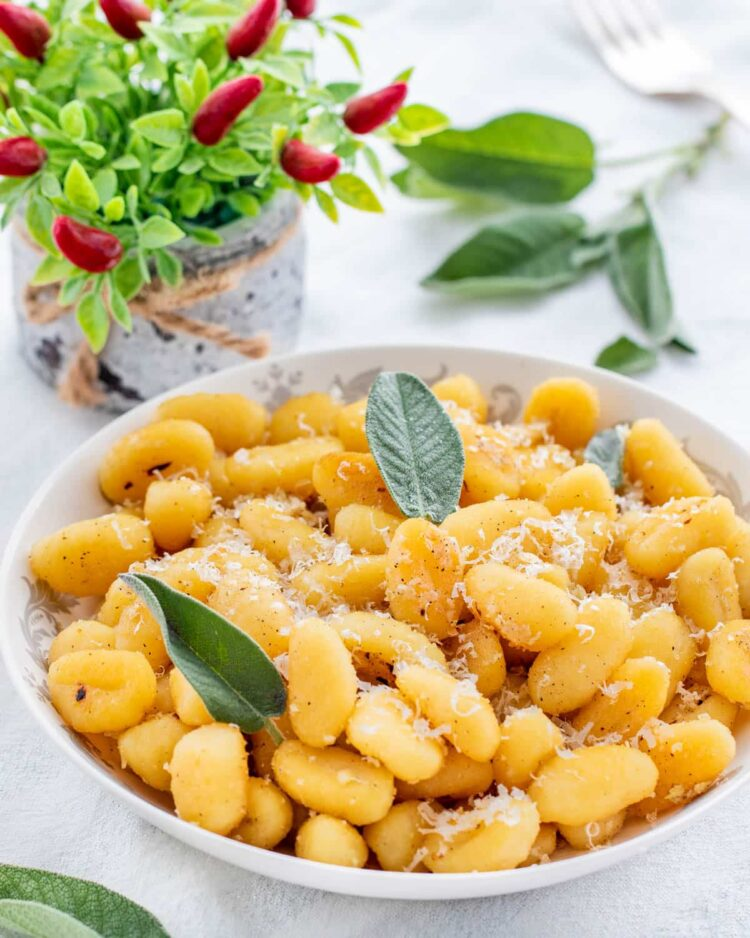 garlic parmasan butter gnocchi in a white plate garnished with sage leaves