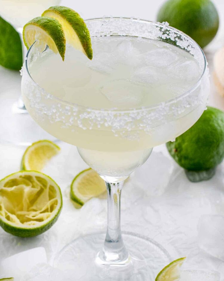 margarita in a rimmed glass with ice and lime wedges