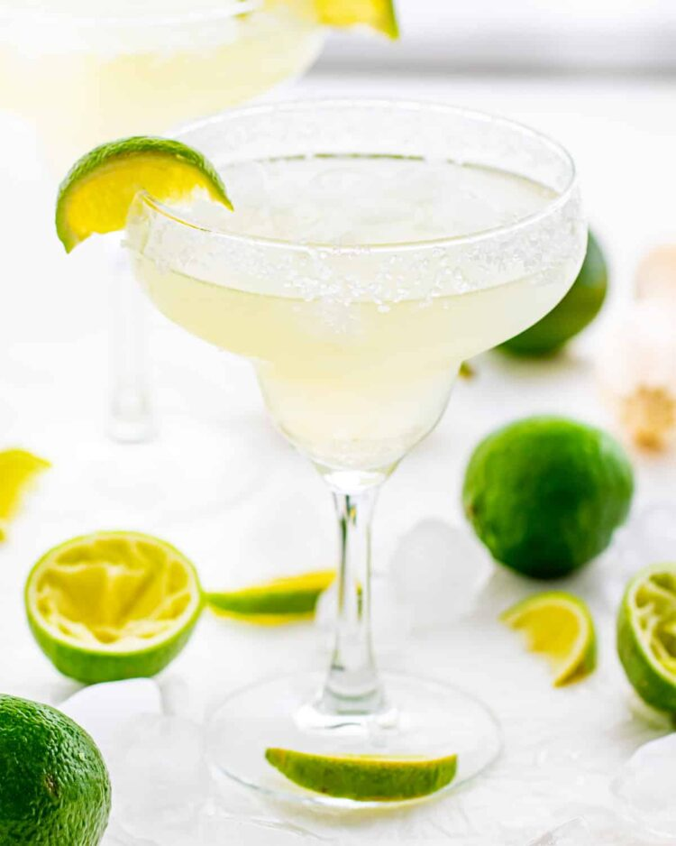 margarita in a rimmed glass with lime wedges