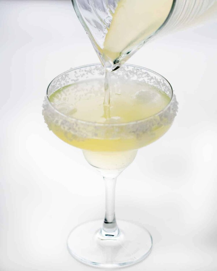 pouring margarita in a rimmed glass