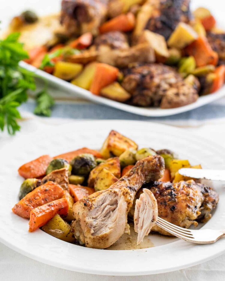 roasted chicken with roasted vegetables on a white plate