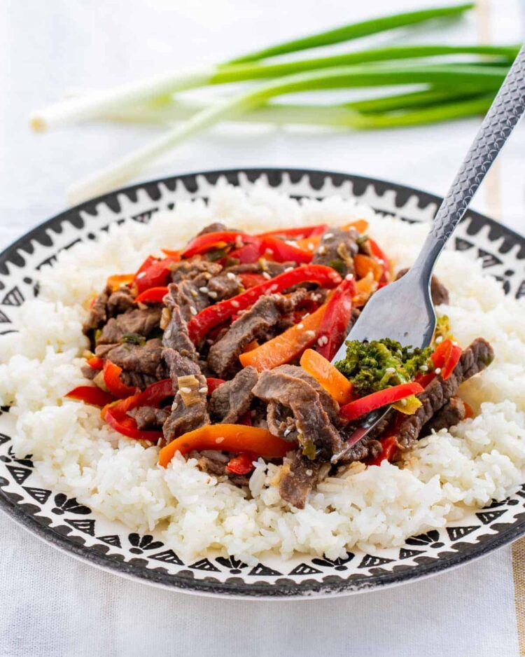 beef stir fry over rice in a plate with a fork in it