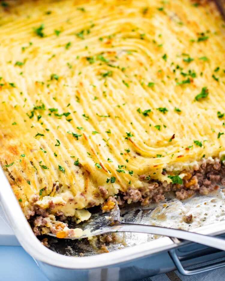 a casserole dish with freshly made shepherd's pie garnished with parsley