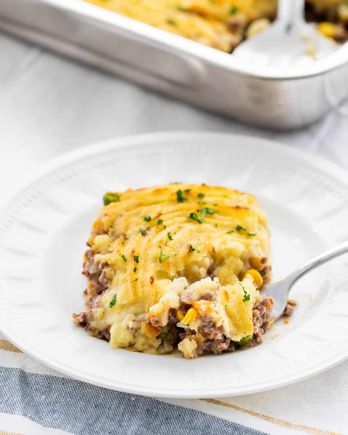 a white plate with a slice of shepherd's pie with a fork in it