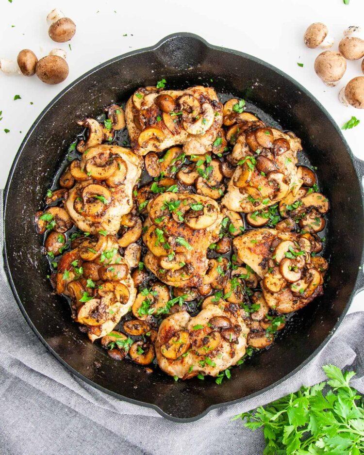 overhead shot of chicken and mushrooms in a skillet