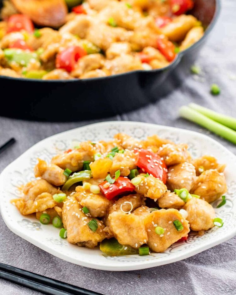 sweet and sour chicken on a white plate with a skillet in the background