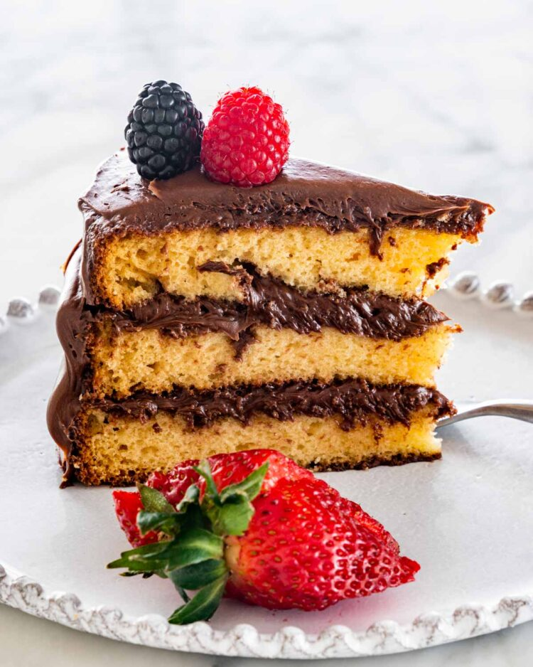 a slice of yellow cake with chocolate frosting and berries