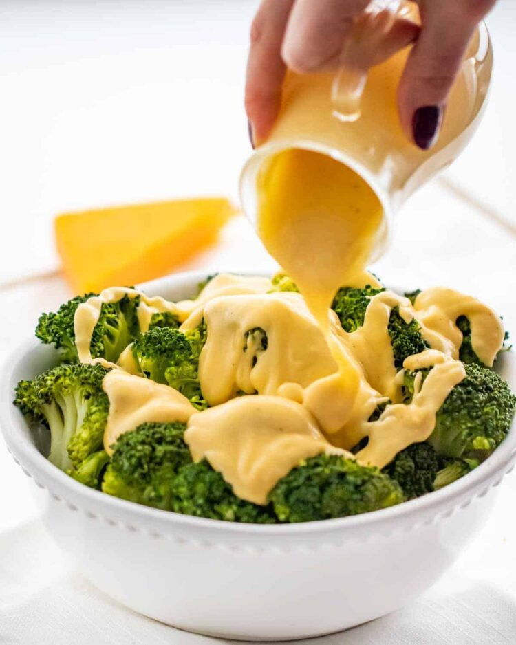 pouring cheese sauce over steamed broccoli