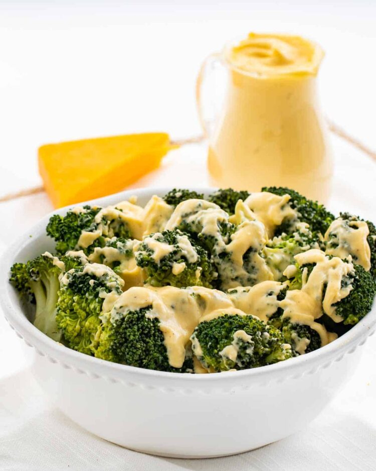 steamed broccoli in a white bowl drizzled with cheese sauce