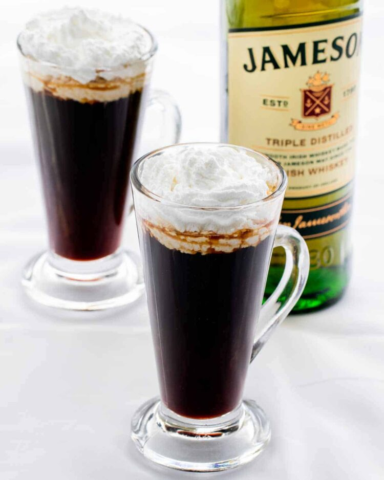 two glass cups with irish coffee and a bottle of whiskey in the background