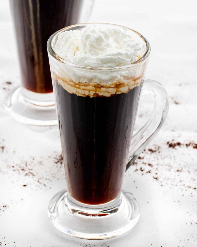 a glass cup with irish coffee topped with whipped cream
